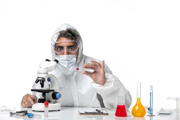 Man arts in beschermend pak met steriel masker met behulp van zijn microscoop op wit
