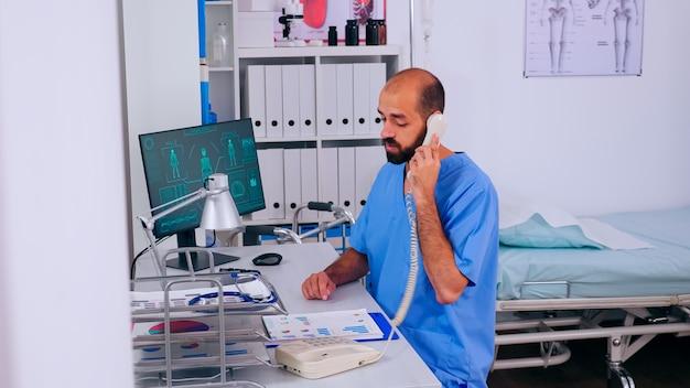 Man arts in de gezondheidszorg die telefoontjes beantwoordt die in de ziekenhuiskliniek werken en de patiënt helpt met een medische afspraak. receptioniste in medicijnuniform, doktersassistente tijdens telezorgcommunicatie