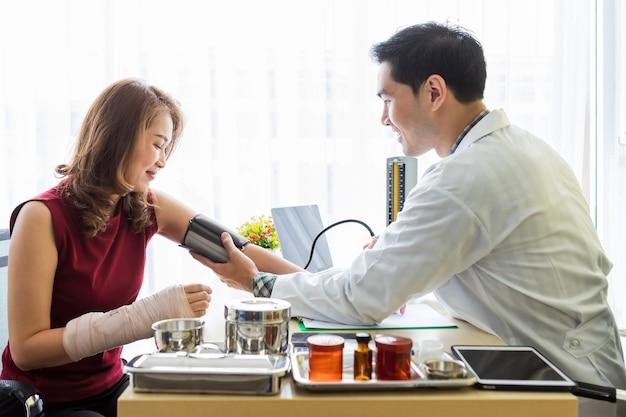 Man arts met het meten van de druk op de arm van een vrouwelijke patiënt draag arm spalk