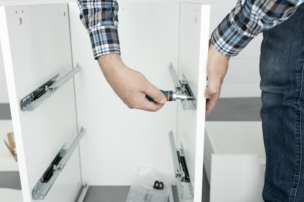 Man assembleert een ladeschuif meubilair met behulp van een schroevendraaier