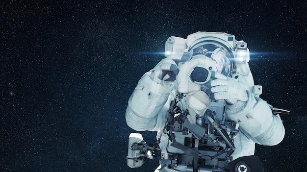 Man astronaut fotograaf maakt een foto op camera in de ruimte met sterren. space man paparazzi, creatief.