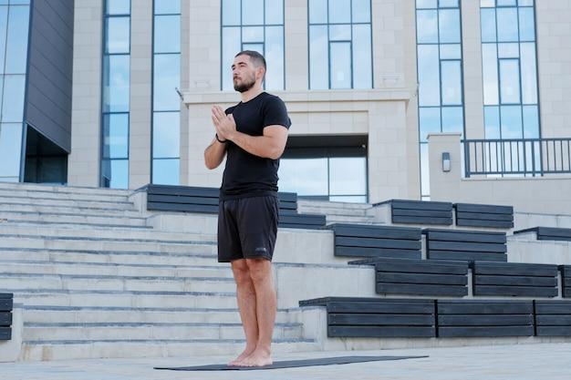 Man atleet in zwarte sportkleding praktijken yoga oefeningen gebedspositie. handen in namaste-houding.