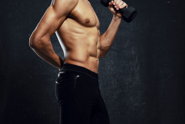Man atleet opgeblazen lichaam training sportschool donkere achtergrond
