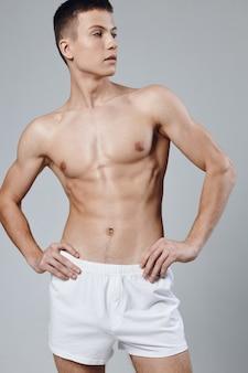Man atleet witte korte broek handen op riem poseren sportschool