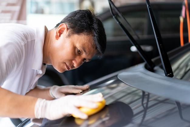 Man auto buitenkant schoonmaken met behulp van spons