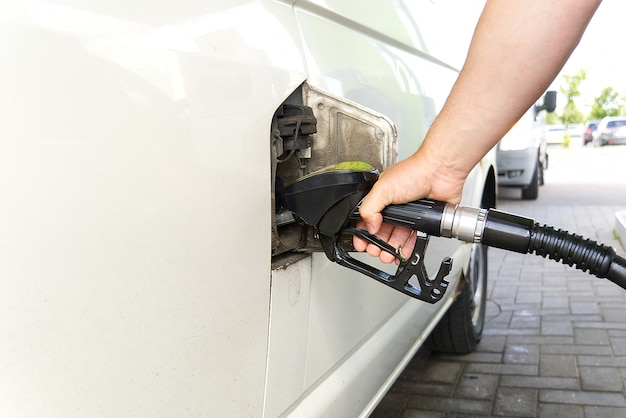 Man auto vullen met diesel. hand met zwarte oliedispenser bij benzinestation