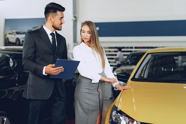 Man autohandelaar een vrouw koper een nieuwe auto in autosalon tonen