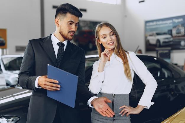 Man autohandelaar een vrouw koper een nieuwe auto tonen