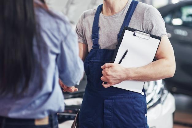 Man automonteur en vrouw klant maken een afspraak over de reparatie van de auto