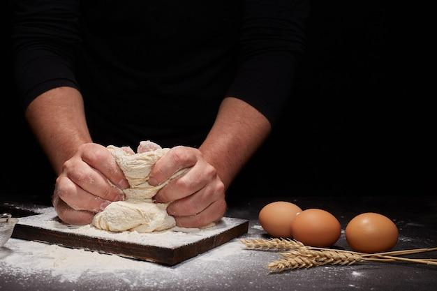Man baker en zijn handen over het brood van volkoren meel