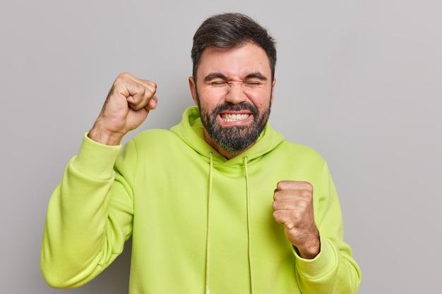 Man balt vuist van geluk verheugt zich iets voelt als winnaar balt tanden gekleed in casual hoodie geïsoleerd op grijs