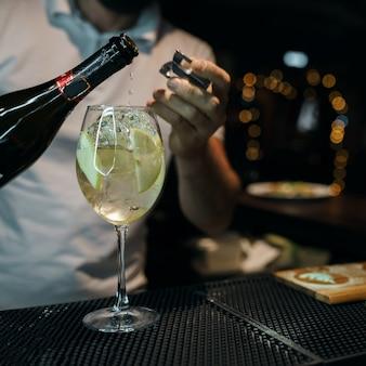 Man barman zoete champagne gieten in een glas met ijs en een plakje appel op een in nachtclub feest. levensstijl