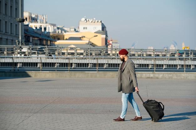 Man bebaarde hipster reizen met grote bagagetas op wielen. laat reizen beginnen. reiziger met koffer arriveert op het treinstation van de luchthaven. hipster klaar geniet van reizen. reistas meenemen. zakenreis.