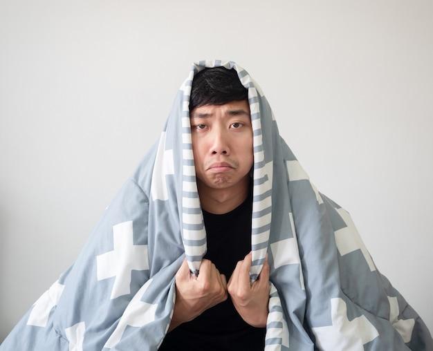 Man bedek hoofd door deken voelt zich verveeld in gezicht kijk naar camera op wit geïsoleerdverveelde slaperige man
