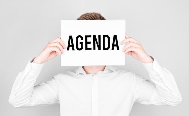 Man bedekt zijn gezicht met een wit papier met de tekst agenda