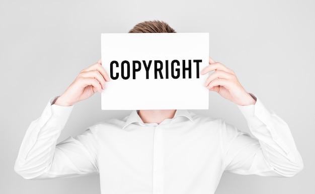 Man bedekt zijn gezicht met een wit papier met de tekst copyright