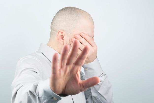 Man bedekt zijn gezicht met zijn hand