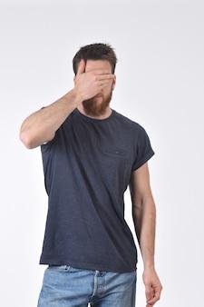 Man bedekt zijn ogen met zijn hand