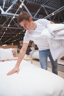 Man behandeling van lakens te koop bij meubels winkel