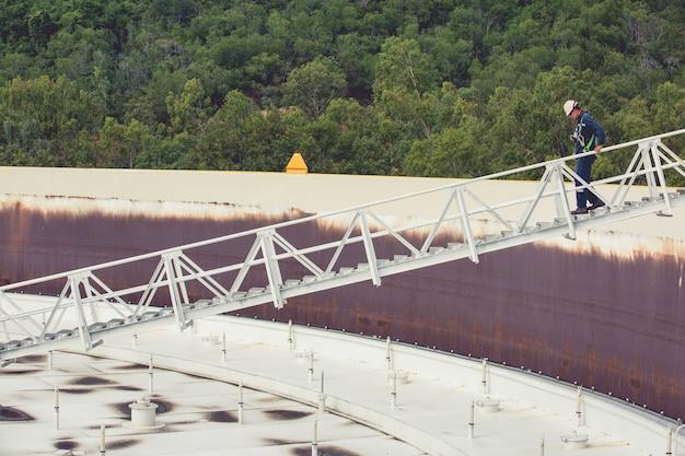 Man beklim de trap opslag dak visuele inspectie tankolie
