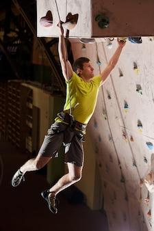 Man beoefenen van rotsklimmen op een rotswand binnenshuis