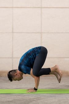 Man beoefenen van yoga buiten op de mat
