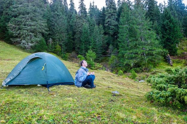 Man beoefenen van yoga in de buurt van blauwe camping tent in een groen bos met pijnbomen
