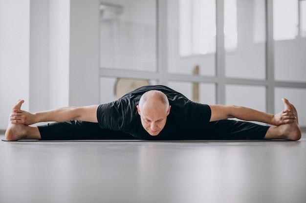 Man beoefenen van yoga in de sportschool