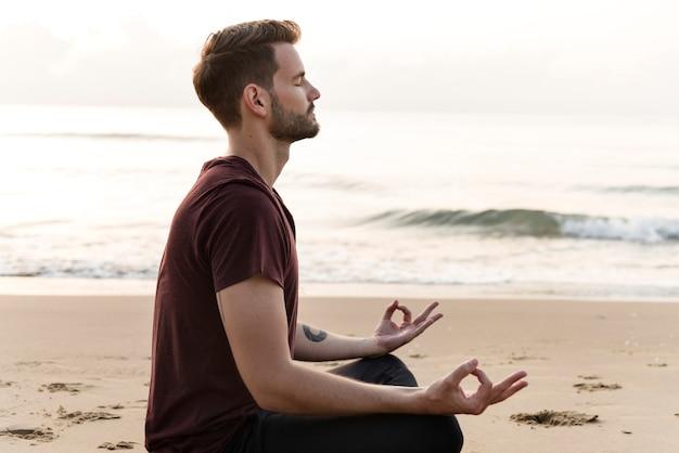 Man beoefenen van yoga op het strand