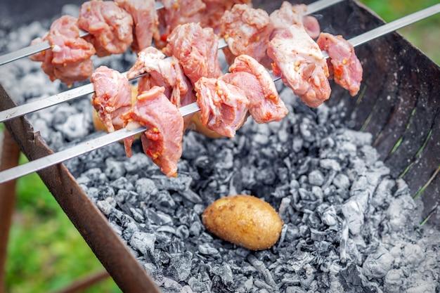 Man bereidt barbecue vlees met aardappelen