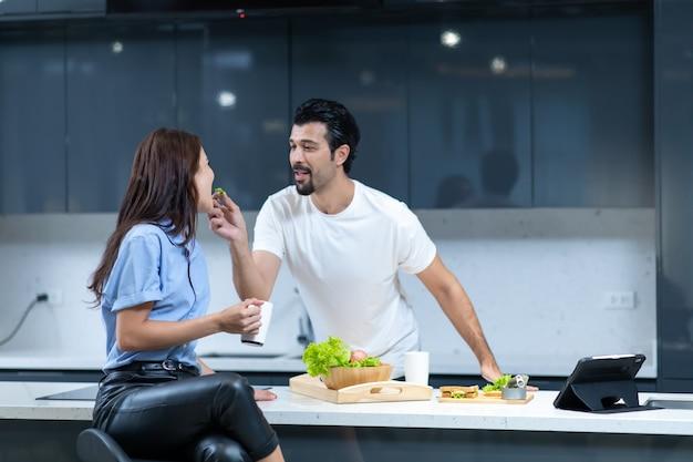 Man bereidt groentesandwich voor zijn vrouw terwijl de vrouw koffie drinkt. gelukkige familie tijd samen doorbrengen thuis.
