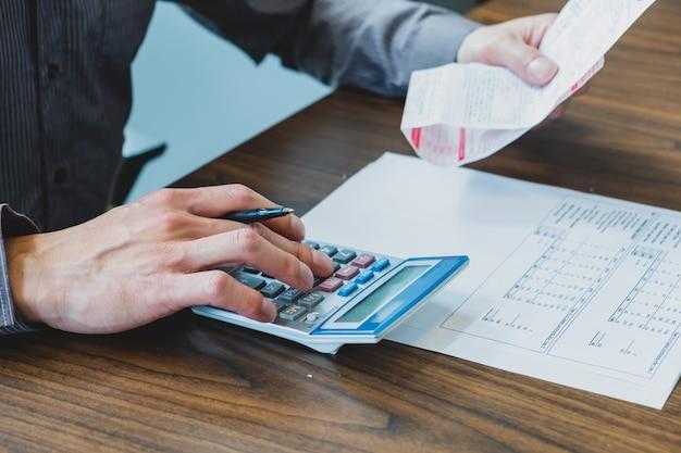 Man berekening van huishoudelijke uitgaven met rekenmachine