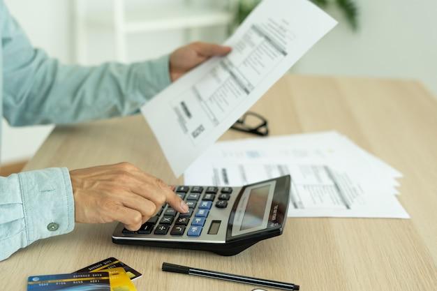 Man berekent de schuld bij de hand met een rekenmachine. de mens is gestrest en overdenkt door schulden van vele creditcards en rekeningen. financieel probleemconcept.