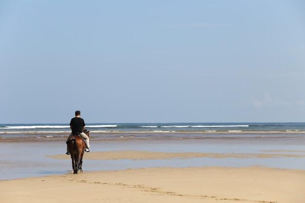 Man berijden van een paard op het strand