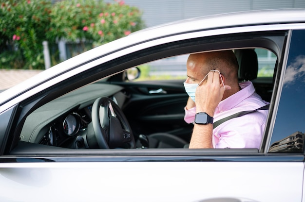Man beschermend masker in de auto zetten