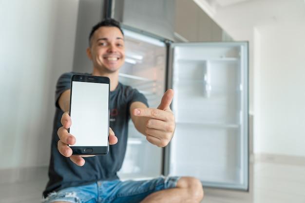 Man bestelt eten met behulp van een smartphone in de buurt van een lege koelkast