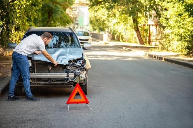 Man bestuurder kijken op smashed gebroken auto in ongeval. rode noodstop driehoek eerder vernietigde auto in auto-ongeluk verkeersongeval op stadsweg. ruimte kopiëren.