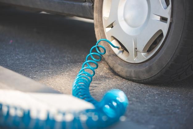 Man bestuurder luchtdruk controleren en lucht in de banden van zijn moderne auto, transport concept vullen