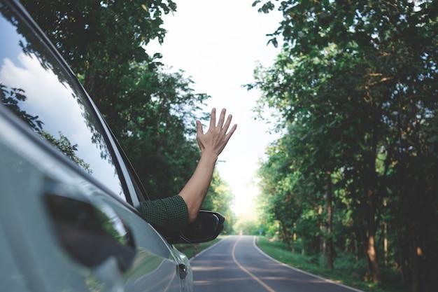 Man bestuurder voelt de wind door zijn handen tijdens het rijden op het platteland.