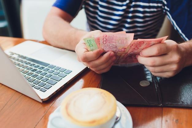 Man betalen factuur in café. hij zet geld op. drukke man met lunch in restaurant. dienstverleningsconcept.