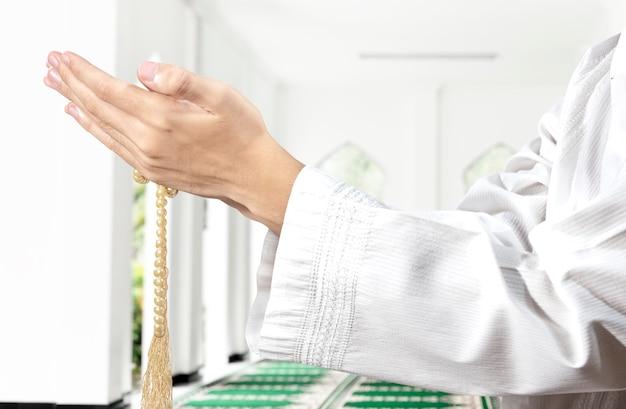 Man bidden met gebedskralen op zijn handen op de moskee