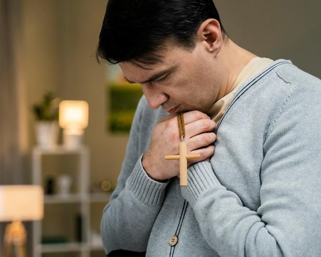 Man bidden met houten kruis