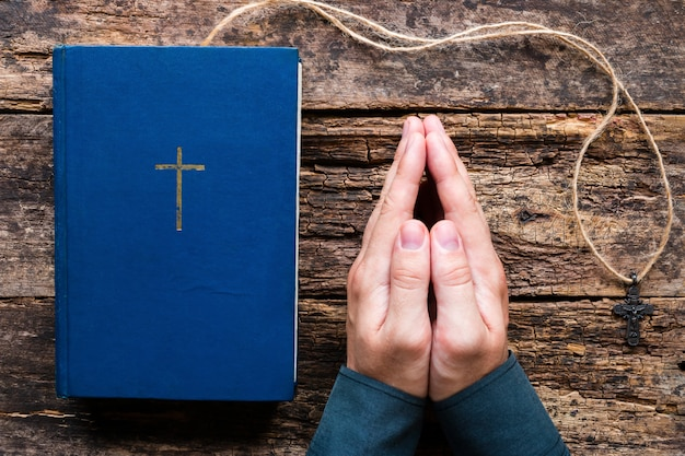 Man bidden naast de bijbel en kruis op een houten achtergrond