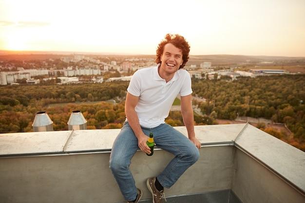 Man bier drinken en ontspannen op het dak