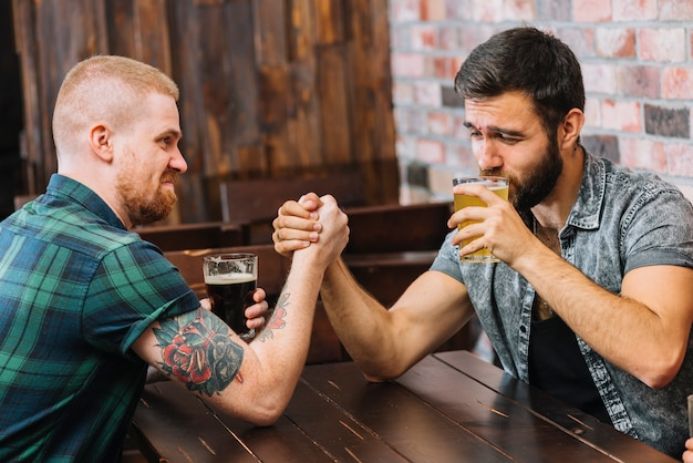 Man bier drinken terwijl arm worstelen met zijn vriend