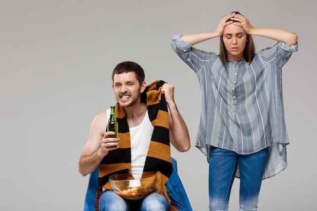Man bier drinken, voetbal kijken en boos vrouw achter