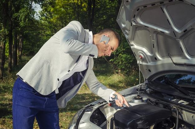 Man bij de open motorkap die een telefoongesprek voert en probeert het voertuig te repareren
