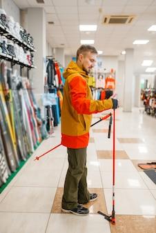 Man bij de showcase skistokken kiezen, winkelen in de sportwinkel.