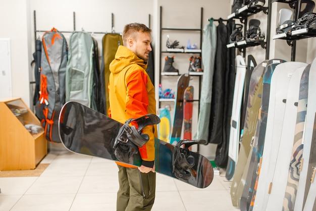 Man bij de showcase snowboard kiezen, winkelen in sportwinkel.