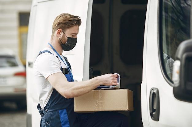 Man bij de vrachtwagen. kerel in een leveringsuniform. man in een medisch masker. coronavirus concept.